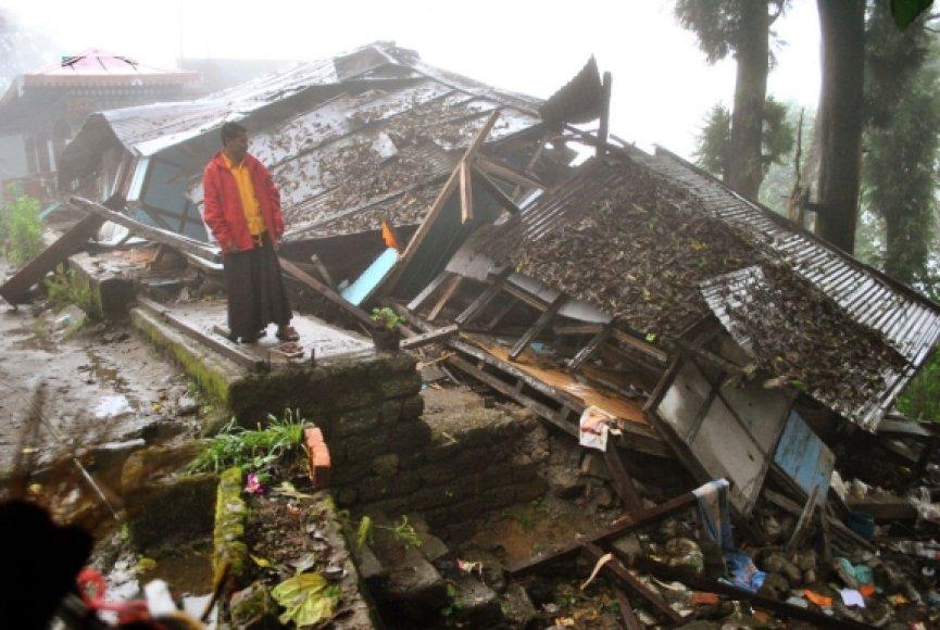Budistų vienuolis stovi ant buvusio vienuolyno griuvėsių