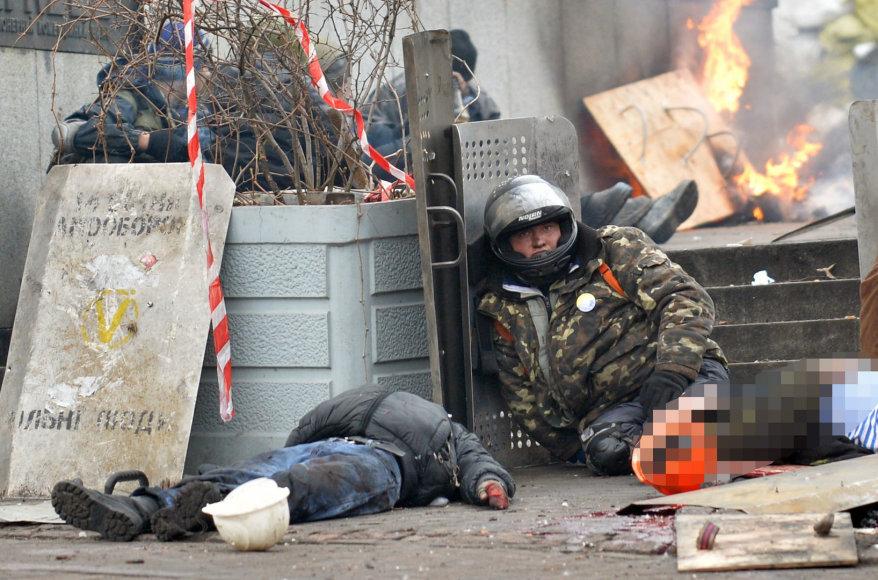 Vyras sėdi šalia dviejų žuvusių protestuotojų