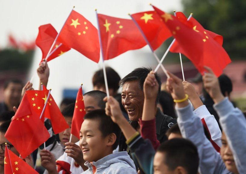 Kinai mojuoja vėliavomis nacionalinės dienos proga Pekine