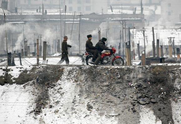 Reuters/Scanpix nuotr./`iaurės Korėjos pasienio pareigūnai linksminasi su motociklu