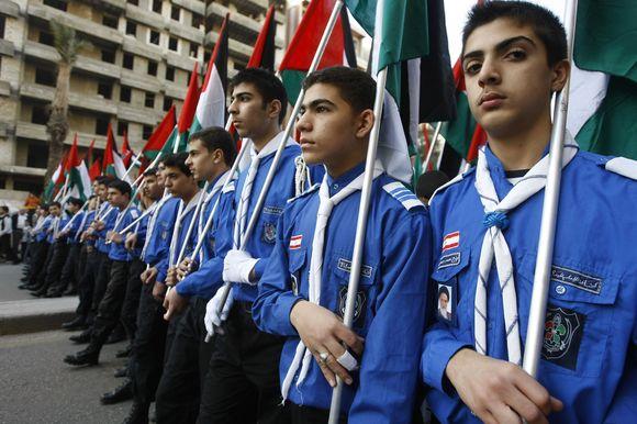 Skautai nešini Palestinos vėliavomis.