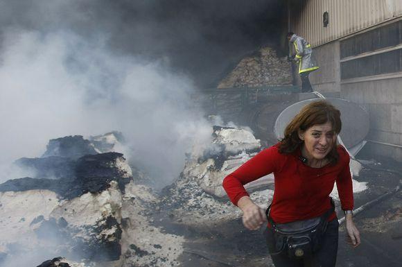 Moteris bėga nuo dūmų.
