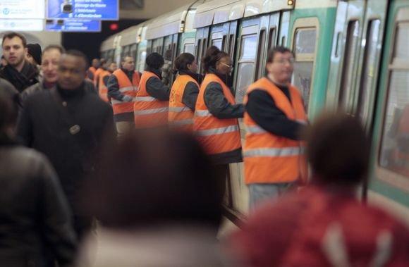 AFP/Scanpix nuotr./Paryžiaus metro gyventojai padeda uždaryti traukinio duris