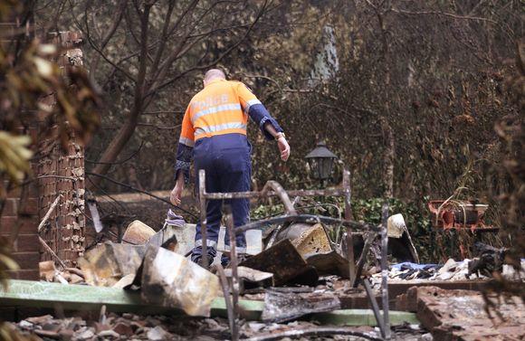 Policijos pareigūnas apžiūrinėja vietą, kur sudegė namas. Jame žuvo penki žmonės.