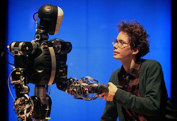Moteris sveikinasi su robotu.