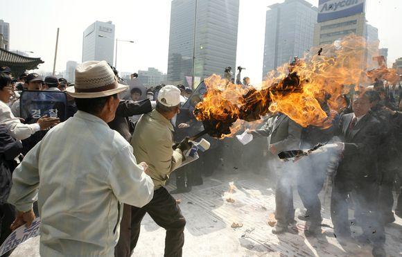 Demonstrantai degina Šiaurės Korėjos vėliavas.