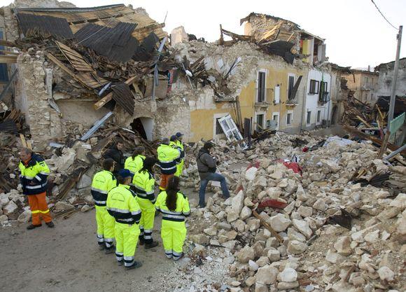 Gelbėtojai apžiūro žemės drebėjimo padarinius.