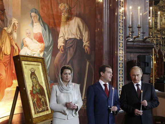 Rusijos prezidentas Dimitrijus Medvedevas (viduryje), jo žmona (kairėje) ir Vladimiras Putinas (dešinėje) dalyvavo velykinėse pamaldose Maskvos ortodoksų bažnyčioje.