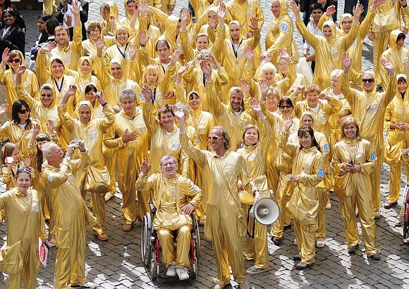 Aukso spalvos kostiumais apsirengę lenkai švenčia istorinių rinkimų dvidešimtmetį.