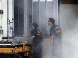 """AFP/""""Scanpix"""" nuotr./Brazilijos pareigūnai apžiūri šaldymo konteinerį, parengtą kūnų saugojimui."""
