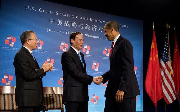 JAV prezidentas Barackas Obama (kairėje) sveikinasi su Kinijos vicepremjeru Wangu Qishanu (centre) ir Kinijos valstybės sekretoriumi Dai Bingguo (kairėje).