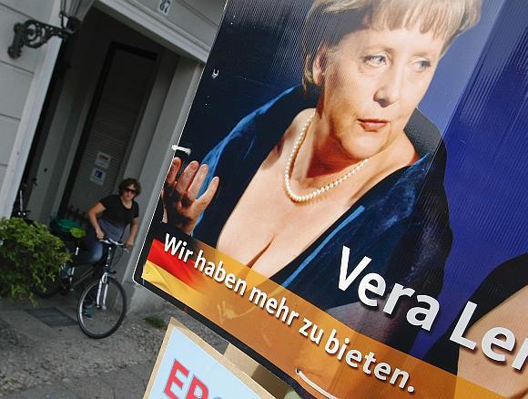 Angela Merkel rinkėjus iš plakatų vilioja ir didele iškirpte