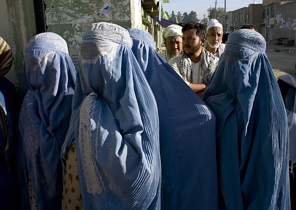 Afganistaniečiai stovi eilėje prie balsavimo apylinkės.