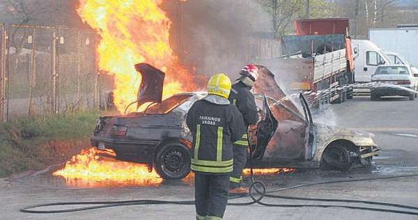 Ugniagesiai gesina automobilį.