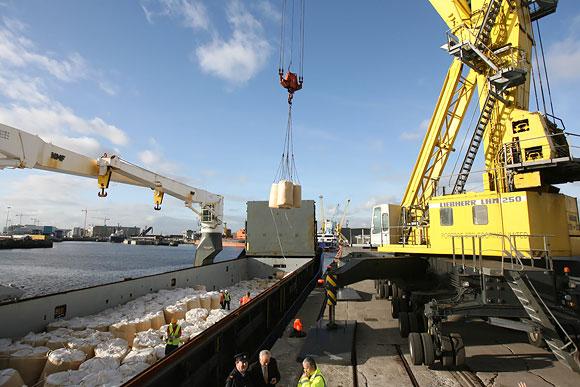 Iš laivo iškraunami maišai su kontrabandiniu kroviniu