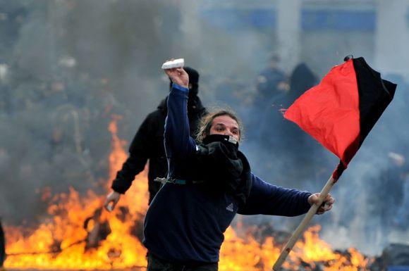 Atėnuose susigrūmė protestuotojai ir policija, kai tūkstančiai žmonių išėjo paminėti prieš metus pareigūno nušauto jaunuolio atminimą.