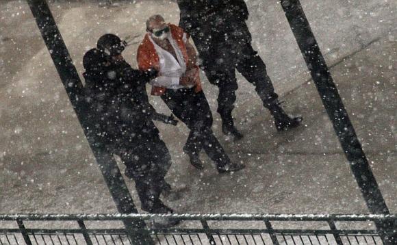 Policininkai išveda įtariamąjį iš banko pastato.