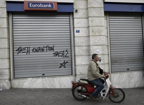 Žmogus važiuoja pro uždarytą banko skyrių Atėnuose.