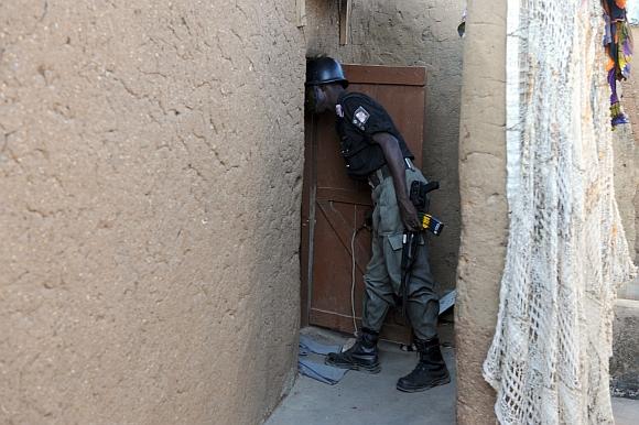 Nigerijos policininkas tikrina islamistų sektos nario namus.