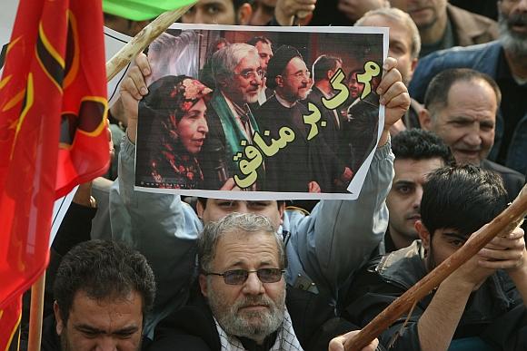 """Vyriausybės šalininkas laiko plakatą, kuriame pavaizduoti buvęs šalies prezidentas Mohammadas Khatamis ir Miras Hosseinas Mousavis su žmona. Užrašas ant plakato skelbia: """"Mirtis veidmaniams""""."""