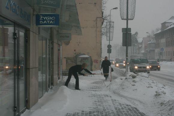 Parduotuvių darbuotojai ryte kasė praėjimus užgriuvusį sniegą.