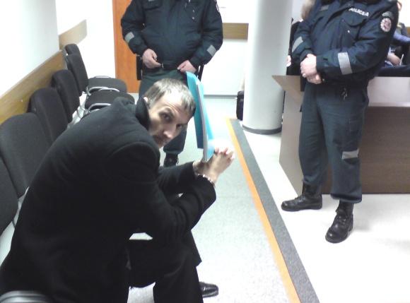 Konvojaus pareigūnų atvežtas ir saugotas kaltinamasis slėpė veidą.