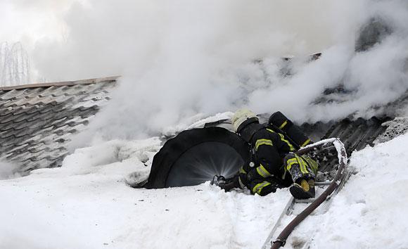 Ugniagesiai ant degančio namo stogo