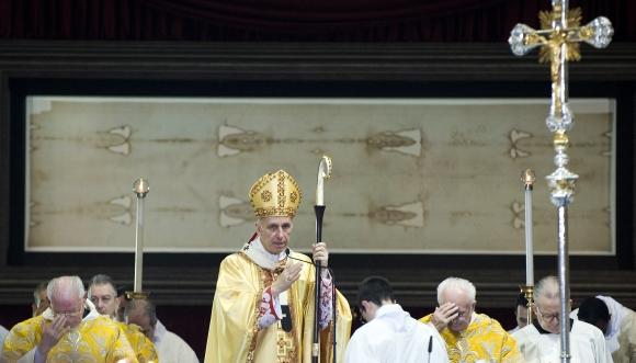 Kardinolas Severino Poletto aukoja Šv. Mišias Turino katedroje žymiosios drobulės fone.