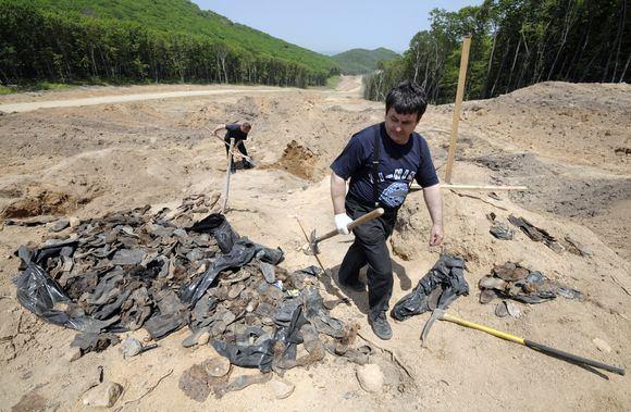 Reuters/Scanpix nuotr./Kelią tiesiantys darbininkai atkasė daugiau kaip 300 Stalino represijų aukų