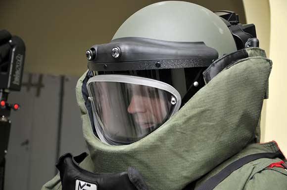 Išminuotojas su apsauginiu kostiumu