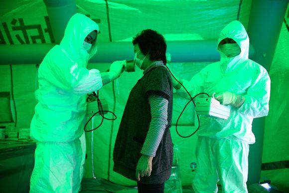 Japonijos medikai radiacijos matuokliais tikrina evakuotą moterį.