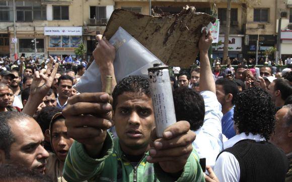 Reuters/Scanpix nuotr./Protestuotojas demonstruoja aovinio tūtelę ir panaudą aaarinių dujų kanistrą.