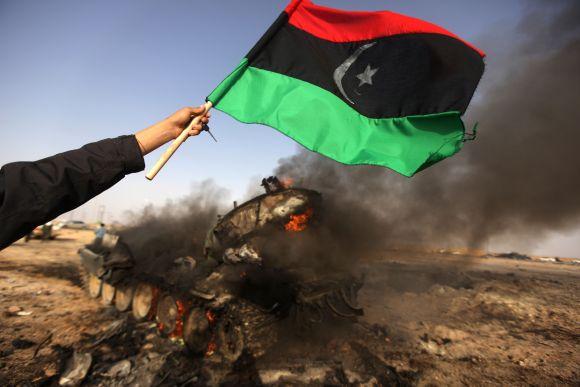 Prie Adždabijos sukilėlis mojuoja vėliava greta degančio tanko.