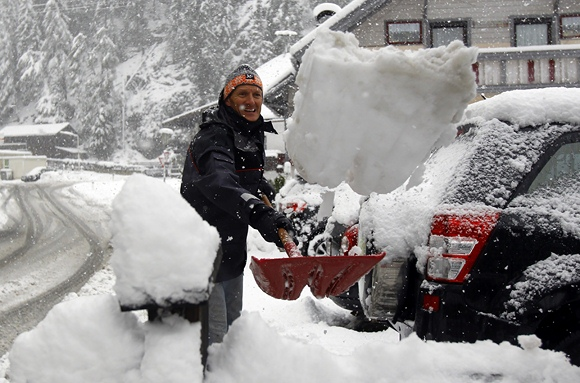 Vyras kasa sniega aplink savo automobilį.