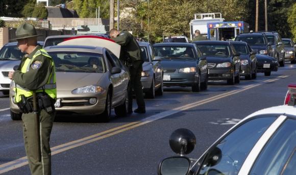 Įtariamojo ieškantys policijos pareigūnai tikrina automobilius.