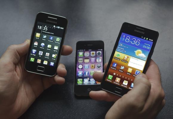 """Vyras rankose laiko """"Samsung Galaxy S II"""" (d.) ir """"Galaxy Ace"""" išmaniuosius telefonus. Fone – """"Apple"""" telefonas """"iPhone 4""""."""