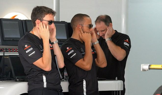 """Lewis Hamiltonas (centre) užsikimešęs ausis kol bandomas """"Formulės-1"""" variklis"""