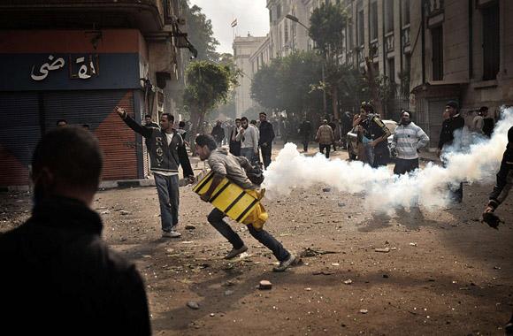 Protestuotojai bėga nuo ašarinių dujų balionėlio.