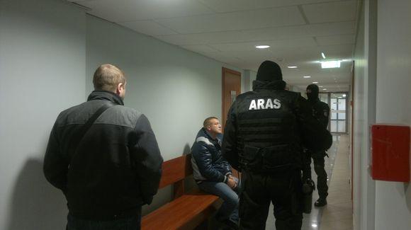 """Įtariamasis (sėdi) ir jį saugantys """"Aro"""" pareigūnai teisme"""