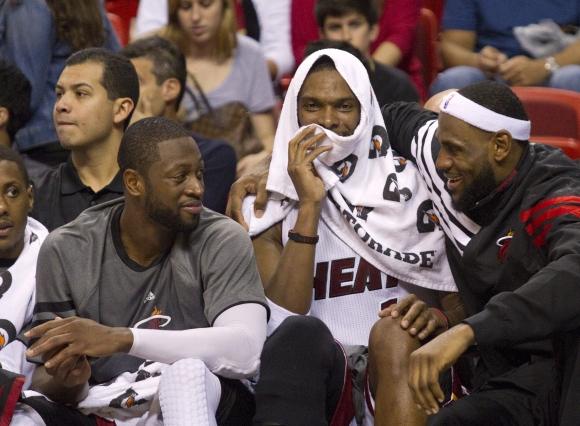 """""""Heat"""" lyderiai Dwyane'as Wade'as, Chrisas Boshas ir LeBronas Jamesas ketvirto kėlinio pabaigoje laiką leido ant atsarginių žaidėjų suolelio."""