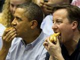 """AFP/""""Scanpix"""" nuotr./JAV prezidentas Barackas Obama ir britų premjeras Davidas Cameronas valgo dešrainius"""