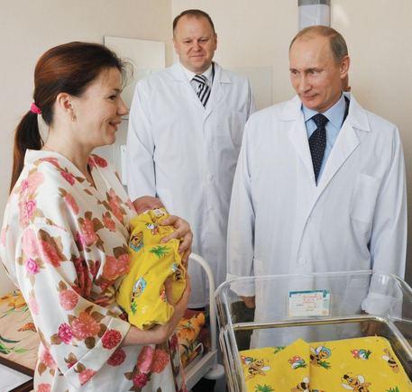 """""""Scanpix"""" nuotr./Septyniamilijardasis pasaulio žmogus, jo mama Jelena Nikolajeva ir Vladimiras Putinas"""