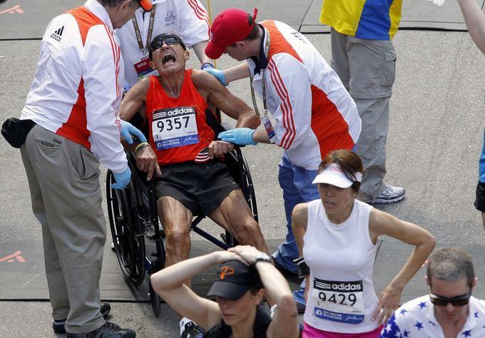Reuters/Scanpix nuotr./Medikai į vežimėlį sodina sunegalavusį Bostono maratono dalyvį.