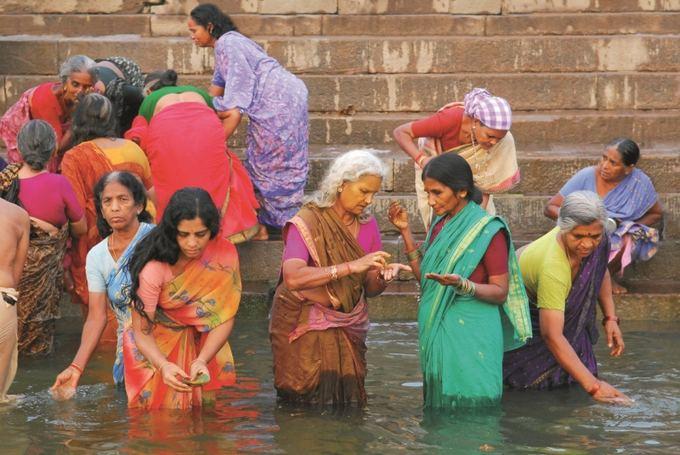 Novaturo nuotr./Spalvingos indų moterys prausiasi Varanasyje