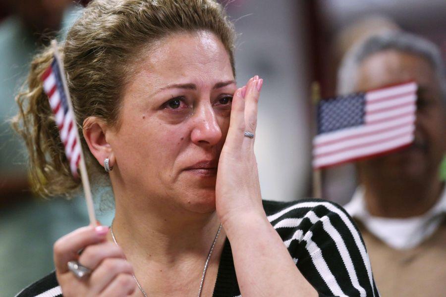 Neseniai pilietybę gavusi moteris braukia džiaugsmo ašarą.