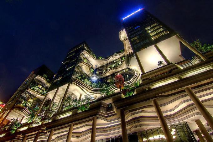 Wikimedia.org nuotr./Parkroyal  stiklinis dangoraižis su vealiomis žaliuojančių medžių ir gėlynų alėjomis