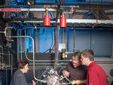NASA Glenno tyrimų centro nuotr./Kuro įpurškimo įrenginio bandymų vadovas Tyleris Hickmanas (vilkintis raudonus marškinėlius) kartu su technikais apžiūrinėja laboratorijoje įrengtą raketinio kuro įpurškimo įrenginį