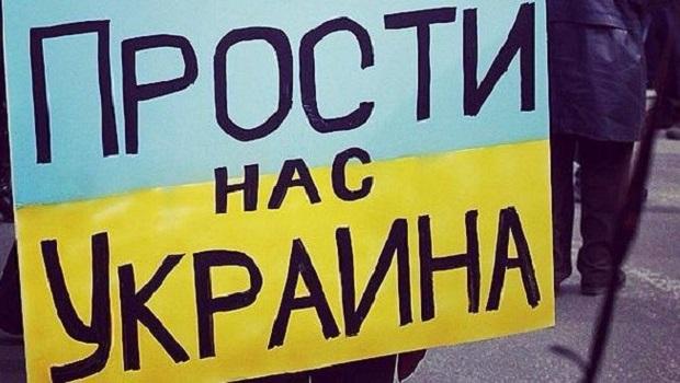 """Protesto prieš karą Ukrainoje dalyviai laiko plakatą su užrašu """"Atlesk mums, Ukraina"""""""