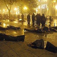 Ant grindinio guli policijos sulaikyti protestuotojai.