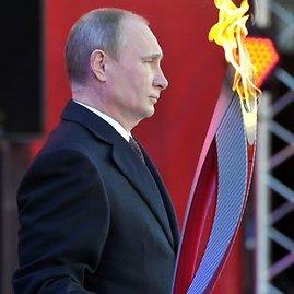 """AFP/""""Scanpix"""" nuotr./Rusijos prezidentas Vladimiras Putinas laiko Sočio olimpinių žaidynių deglą."""